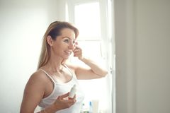 Beautiful blond woman applying face cream. Beautiful blond woman in blue jeans and white shirt standing in home bathroom and applying face cream under her eyes royalty free stock photo