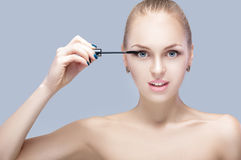 Beautiful blond woman applying makeup on face on gray background. perfect makeup.  brush of mascara Royalty Free Stock Image