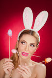 Beautiful blond woman as Easter bunny with rabbit ears on red background, studio shot. Young lady holding three colored eggs stock photo