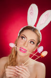Beautiful blond woman as Easter bunny with rabbit ears on red background, studio shot. Young lady holding three colored eggs Royalty Free Stock Photography