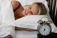 Beautiful Blond Woman Asleep in Bed. Cute blond woman waking up in bed with alarm clock Stock Image