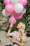 Beautiful blond woman, with balloons, in pink. Smiling and happy, walking in the park. royalty free stock photos