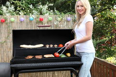 Beautiful blond woman barbecuing on a patio. Standing in front of a gas fire cooking fresh vegetables and meat Royalty Free Stock Image