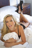 Beautiful Blond Woman on Bed In Black Lingerie Royalty Free Stock Photos