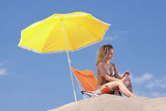 Beautiful blond woman in bikini. With bottle of water on beach Royalty Free Stock Photography
