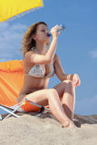Beautiful blond woman in bikini with bottle. Of water on beach Royalty Free Stock Photos