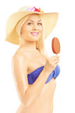 Beautiful blond woman in bikini eating an ice cream Stock Images