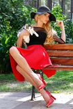 Beautiful blond woman in a black hat with long legs sitting on a bench holding the cute cat Royalty Free Stock Photo