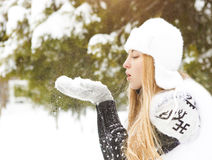 Beautiful blond woman blowing snow outdoors. In winter park Stock Photos