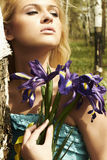 Beautiful blond woman with blue flowers in a forest Stock Images