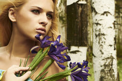 Beautiful blond woman with blue flowers in a forest Royalty Free Stock Photo