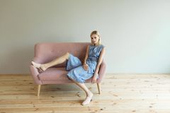 Beautiful blond woman in blue overalls in a light pink shoes sitting on a pink sofa. Fashion model. Royalty Free Stock Photo