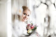 Beautiful blond woman with bouquet posing in a wedding dress royalty free stock image