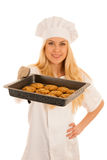 Beautiful blond woman in chef dress bakes cookies isolated over. White background Royalty Free Stock Photo