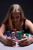 Beautiful blond woman with chips in casino royalty free stock images