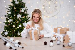 Beautiful blond woman with Christmas gifts sitting in living roo royalty free stock photo
