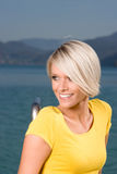 Beautiful blond woman at the coast. Beautiful smiling blond woman in a yellow summer top standing in the sunshine at the ocean with a mountainous coastline in Royalty Free Stock Photography