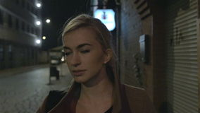 Beautiful blond woman in coat walking alone outdoors at night. Grain. Slow motion.
