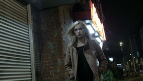 Beautiful blond woman in coat walking alone outdoors at night. Grain. Slow motion. stock footage