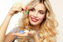 Beautiful blond woman with contact lenses box. Pretty blonde woman pulls out a tweezers contact lens from the box royalty free stock image