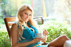 Beautiful blond woman with cup of coffee in summer cafe Royalty Free Stock Photos