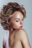 Beautiful blond woman with curly hairstyle royalty free stock photography