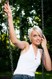 Beautiful blond woman daydreaming on a swing Royalty Free Stock Photo