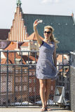Beautiful blond woman doing self-portrait on smartphone from the observation deck at Warsaw. Stock Photography