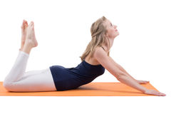 Beautiful blond woman doing stretching muscles of the back, legs, hips, buttocks on a mat Royalty Free Stock Photos