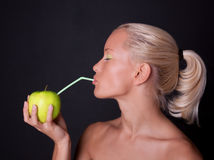 Beautiful blond woman drinking apple juice. With straw Royalty Free Stock Images