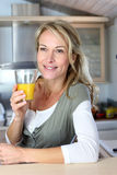 Beautiful blond woman drinking fruit juice. Portrait of blond woman in kitchen drinking orange juice Royalty Free Stock Images