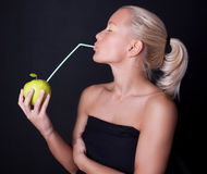 Beautiful blond woman drinking juice with straw. Beautiful blond woman drinking apple juice with straw Stock Photos