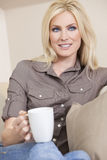 Beautiful Blond Woman Drinking Tea or Coffee. A beautiful young blond woman drinking tea or coffee from a white mug sitting at home on a her sofa Stock Photo
