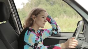 Beautiful blond woman is driving and calling by phone stock footage