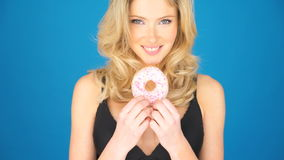 Beautiful blond woman eating a big doughnut stock video footage