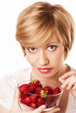Beautiful blond woman eating strawberries Stock Photo