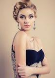 Beautiful blond woman in elegant black dress Stock Photos