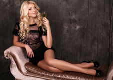 Beautiful blond woman in elegant dress,with glass of champagne Royalty Free Stock Photography