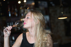 Beautiful blond woman enjoying a glass of champagne or prosecco Royalty Free Stock Photography