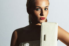 Beautiful blond woman.Fashion people.Stylish girl with white clutch.Red lips Royalty Free Stock Image