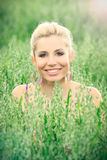 Beautiful blond woman in a field. Portrait of beautiful blonde in a oat field, fashion photography Royalty Free Stock Photos