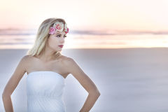 A beautiful blond woman with a floral headpiece on standing on beach at sunrise. Stock Photography