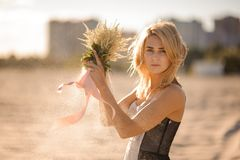 Beautiful blond woman with flowers in hands Stock Photo