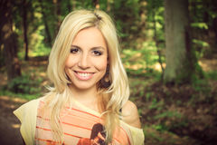 Beautiful blond woman in a forest. Portrait of beautiful blonde in a yellow shirt in a forest, in a nature, fashion photography Royalty Free Stock Images