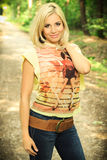 Beautiful blond woman on a forest road Royalty Free Stock Image
