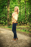 Beautiful blond woman on a forest road Stock Images