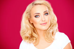 Beautiful blond woman with a gentle smile. And gorgeous grey blue eyes looking at the camera on a pink background Royalty Free Stock Photography