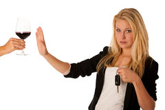 Beautiful blond woman gesturing don't drink and drive gesture, w. Ith refusing a glass of red wine isolated over white Royalty Free Stock Photos