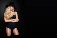 Beautiful blond woman girl sexy model dressed in black lingerie outfit body swimsuit and black hat Royalty Free Stock Photo