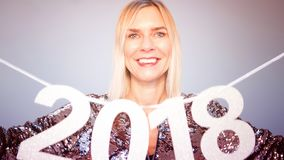 Blond woman in glitter dress holding the numbers 2018. Beautiful blond woman in glitter dress holding the numbers 2018 Stock Image